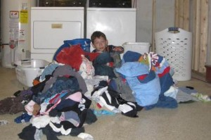 8 year old buried in laundry1 300x199 Getting Kids to Help At Home