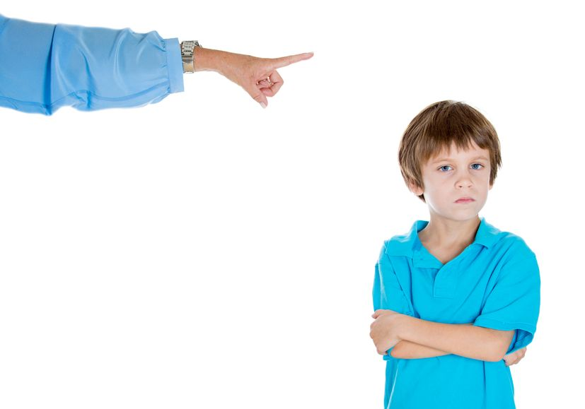 closeup portrait of parent pointing at child to go to room for misbehaving while kid is upset with arms folded. isolated on white background.